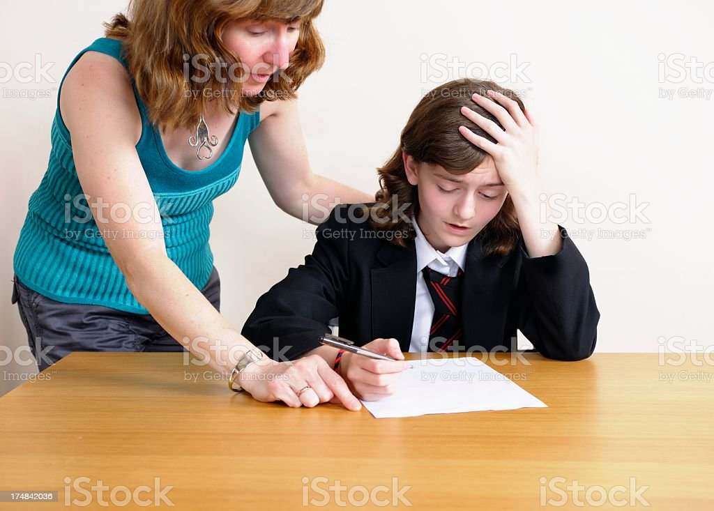 Parent/ Carer Assisting Schoolgirl  Who Is Struggling With Homework royalty-free stock photo
