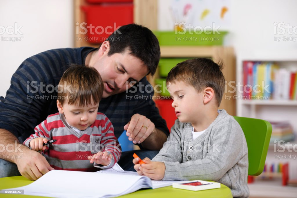 Parent/ Carer Interacting With Toddler And Older Son/ Child stock photo