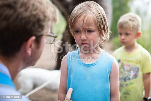 Young boy looks sad and down while his father corrects him for something he did wrong