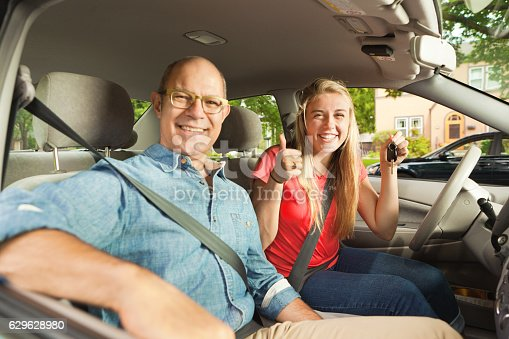 istock Parent Driving Instructor and Happy Teenage Student Driver in Car 629628980