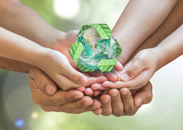 parent guardian children hands holding together recycled green leaf arrow sign planet on blur nature greenery background sun flare environment csr esg concept element of this image furnished by nasa - biodegradabile foto e immagini stock