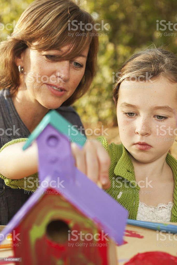 Parent Helping Child with a Birdhouse Painting Project Vt royalty-free stock photo