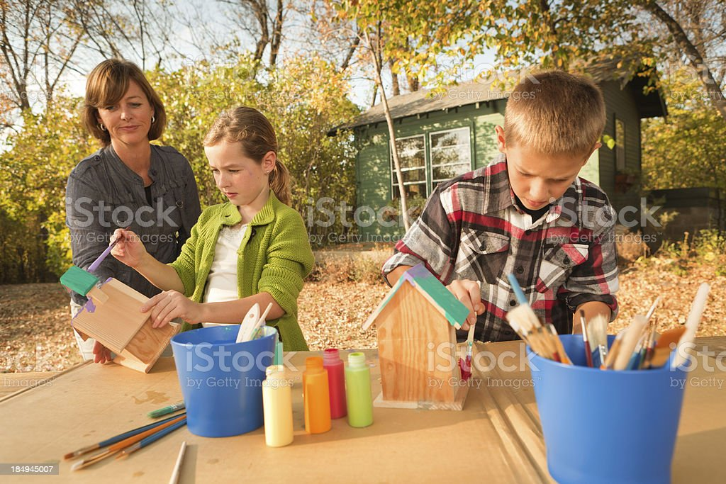 Parent Helping Children in Birhouse Painting Project Hz royalty-free stock photo