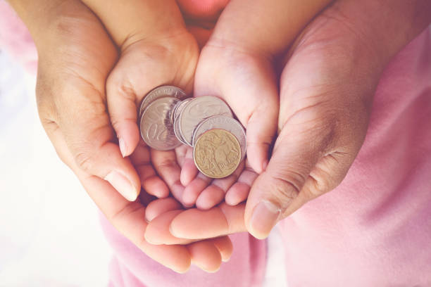 parent holding child hands with Australian money stock photo