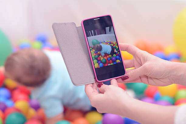 Eltern Fotografieren Kind mit Smartphone – Foto