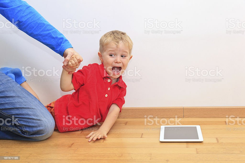 Parent pulling child from touch pad. Computer Addiction stock photo