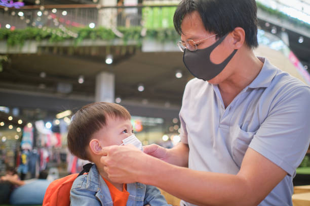 Parent putting mask on his Asian toddler boy child, Dad and son wearing protective medical mask in public area, shopping center Parent putting mask on his Asian toddler boy child, Dad and son wearing protective medical mask in public area, shopping center, Concept of coronavirus quarantines and Air pollution pm2.5 in Thailand thailand mall stock pictures, royalty-free photos & images