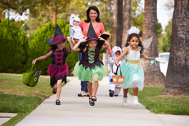 Parent Taking Children Trick Or Treating At Halloween stock photo