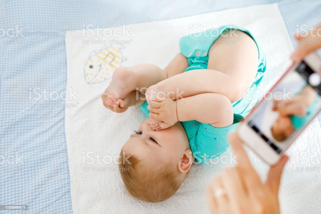 Eltern nehmen Foto eines Babys mit Smartphone. Entzückende Neugeborene unter Fuß im Mund – Foto