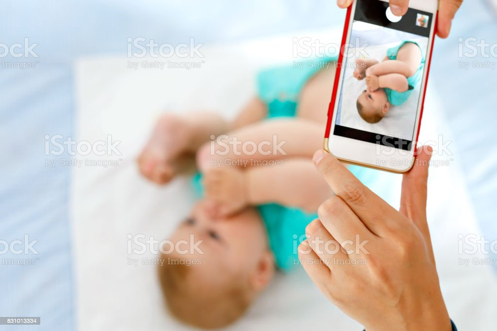 Parent taking photo of a baby with smartphone. Adorable newborn child taking foot in mouth stock photo