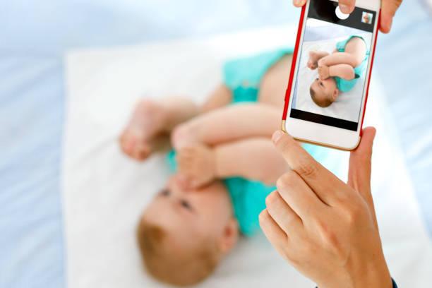 eltern nehmen foto eines babys mit smartphone. entzückende neugeborene unter fuß im mund - lustige babybilder stock-fotos und bilder