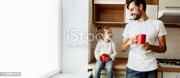 istock Parenthood. Family. Love. Dad and his little daughter are holding red cups, looking at each other and smiling. In the kitchen at home 1130691472