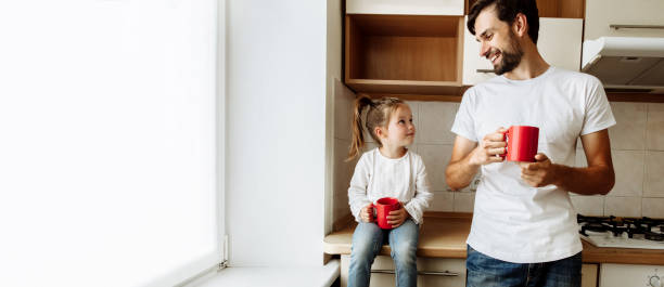 paternidade. família. amor. o paizinho e sua filha pequena estão prendendo copos vermelhos, olhando-se e sorrindo. na cozinha em casa - chá bebida quente - fotografias e filmes do acervo