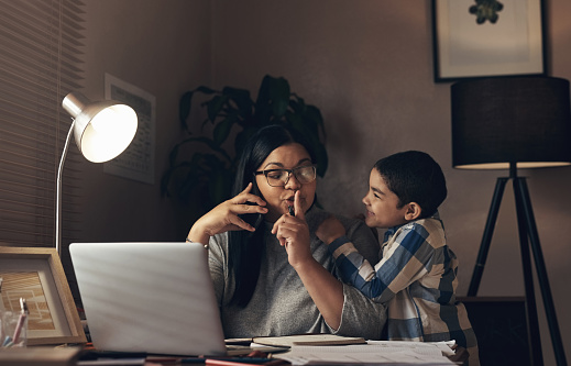 Shot of an adorable little boy demanding his mother's attention while she works at home