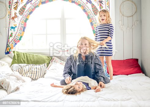 Mother in pajamas with coffee sits on the bed while children jump all around her