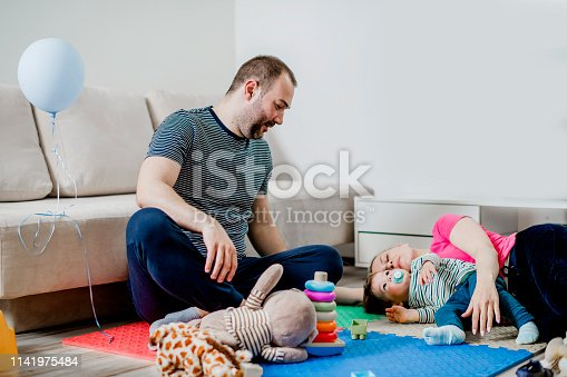 872316662 istock photo Parents and a little boy playing with toys 1141975484
