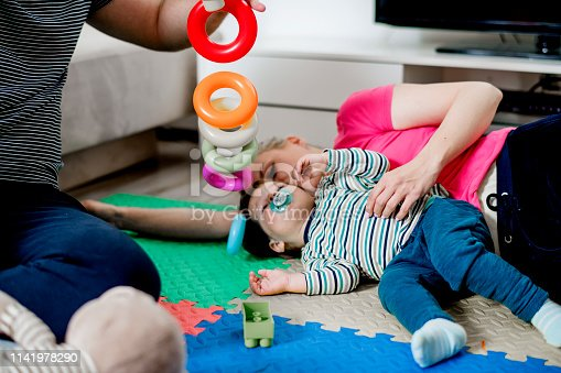 872316662 istock photo Parents and a little boy playing with toys 1141978290
