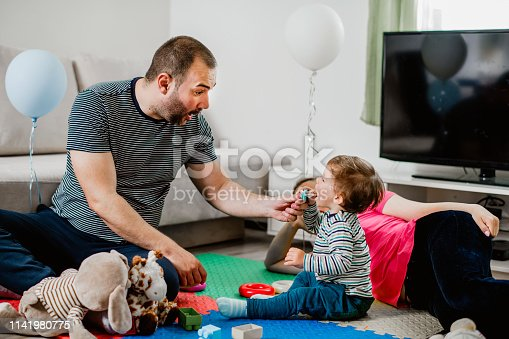 872316662 istock photo Parents and a little boy playing with toys 1141980775