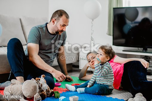 872316662 istock photo Parents and a little boy playing with toys 1141982574