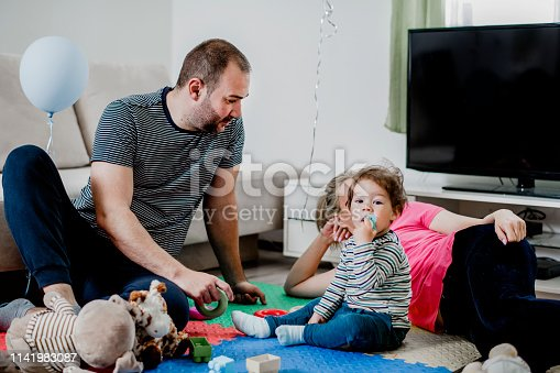 872316662 istock photo Parents and a little boy playing with toys 1141983087