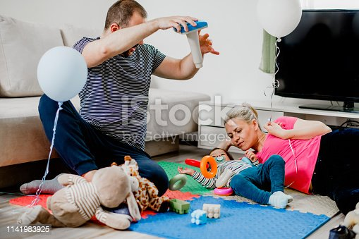 872316662 istock photo Parents and a little boy playing with toys 1141983925