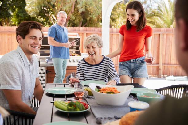 los padres y los hijos adultos tener una barbacoa en el jardín - couple lunch outdoors fotografías e imágenes de stock