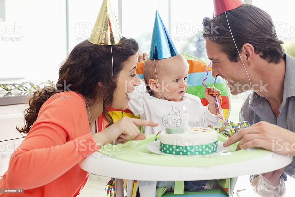 Parents and baby celebrating first birthday stock photo