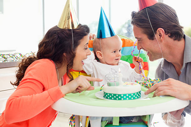 Parents and baby celebrating first birthday  first birthday stock pictures, royalty-free photos & images