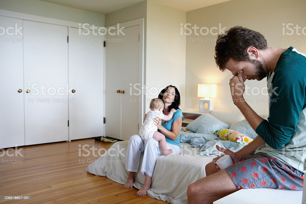 Parents and baby girl (9-12 months) in bedroom, man holding head stock photo