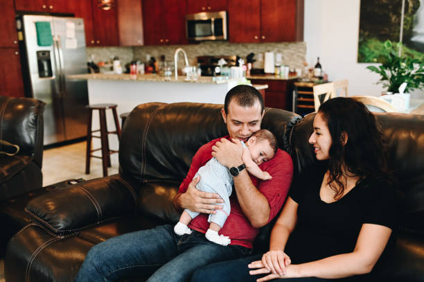 Parents and baby sitting on the couch in the living room, candid young family togetherness at home stock photo