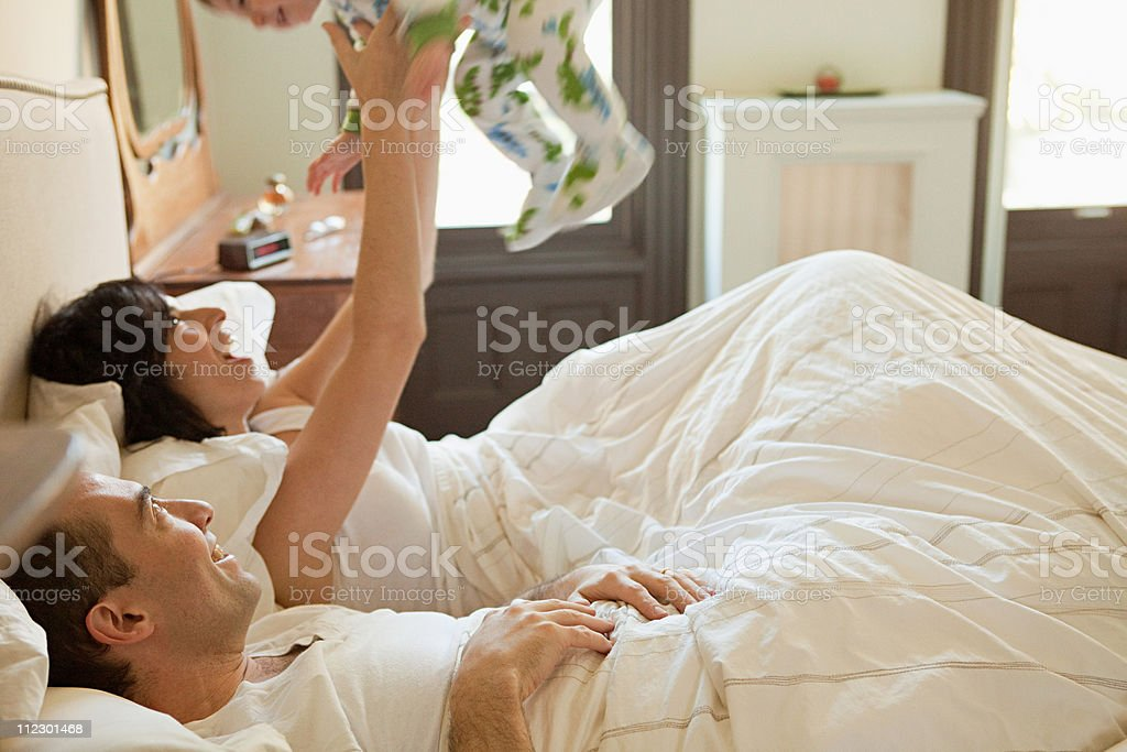 Parents and baby son having a lie in stock photo