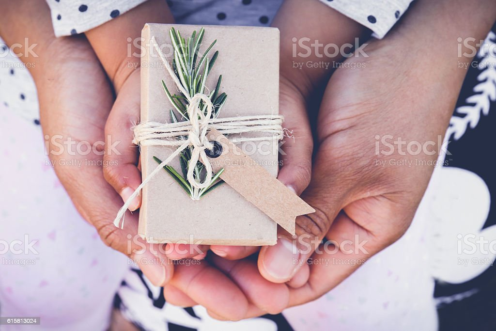 parents and child holding eco gift box with brown tag stock photo