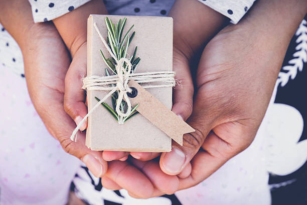 parents and child holding eco gift box with brown tag - bastelkarton stock-fotos und bilder
