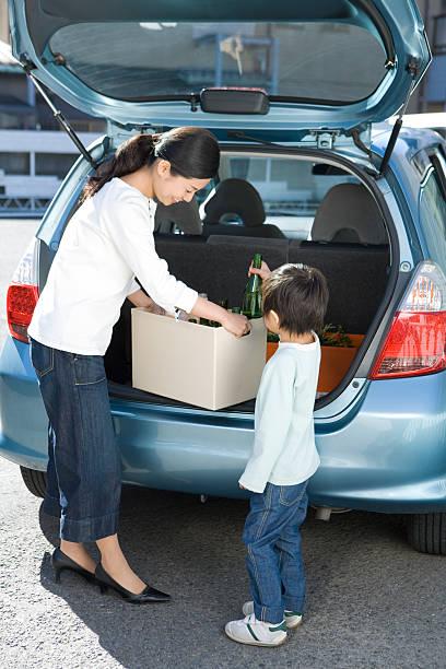 Los padres y el bebé carga los frascos vacíos en automóvil - foto de stock