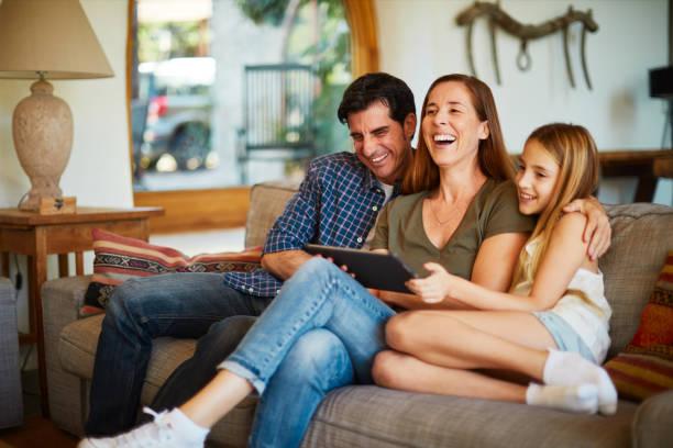 Eltern und Kinder streamen Medieninhalte von einem digitalen Tablet. – Foto