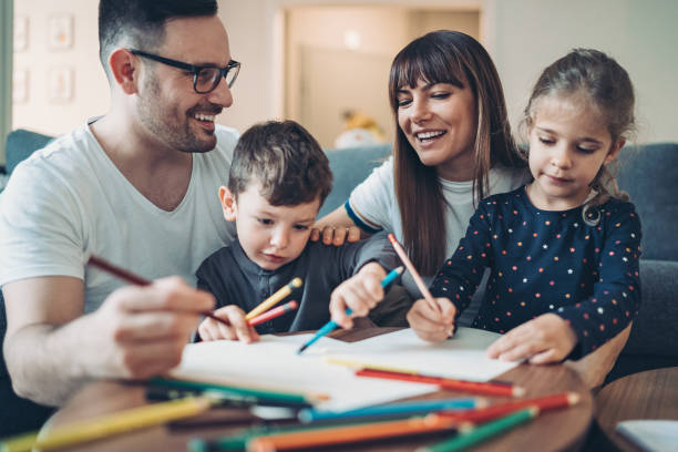Parents and children coloring pages together stock photo