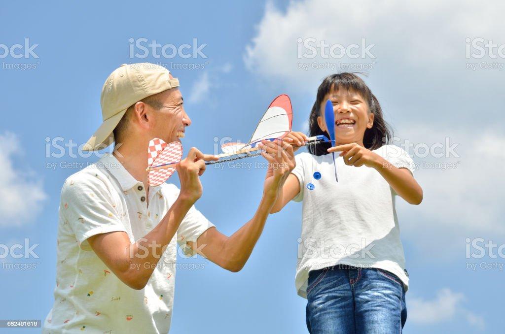 青空に模型飛行機を飛ばす親子(夏) royalty-free stock photo