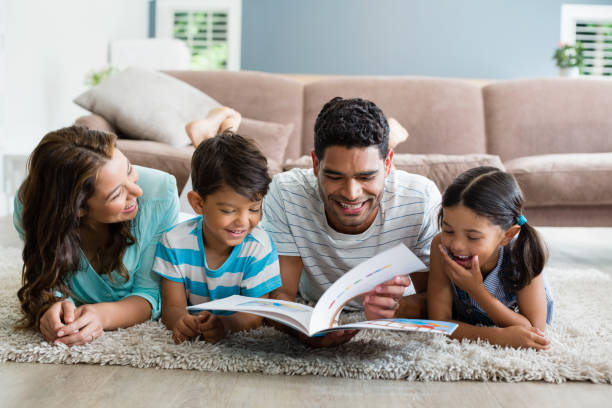 Parents and children lying on rug and reading book in living room stock photo