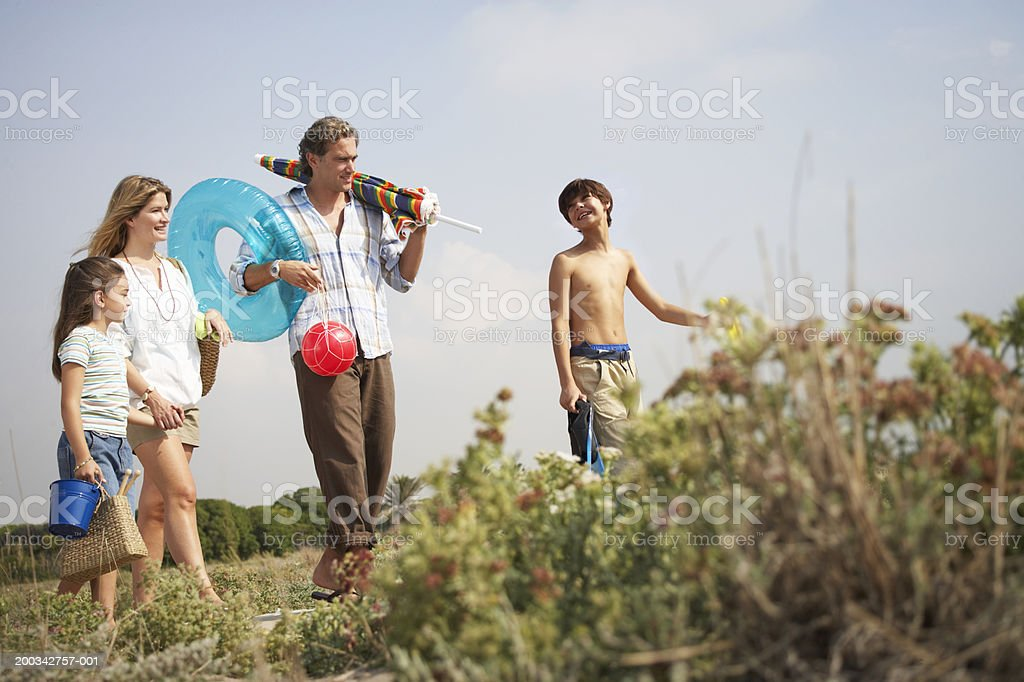 Parents and children (7-9) on path carrying beach toys and parasol royalty-free stock photo