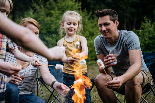 Front view of mid adult mother and father roasting marshmallows over fire with 5 and 6 year old son and daughter during camping trip.
