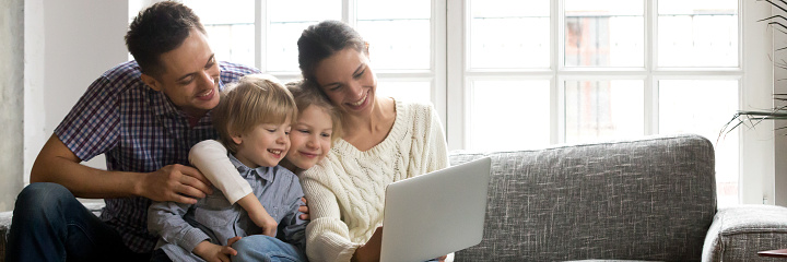 Parents little kids sitting on couch using computer watching video, family enjoy time together, buying online modern tech easy usage concept, banner for website header design with copy space for text