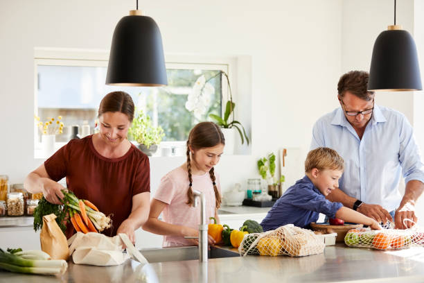 parents and children unpacking grocery in kitchen - grocery home foto e immagini stock