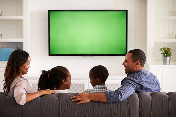 parents and children watching tv, looking at each other - family watching tv stock photos and pictures