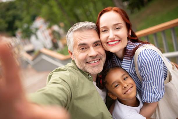 Eltern und Tochter lächeln breit, während sie für Foto posieren – Foto