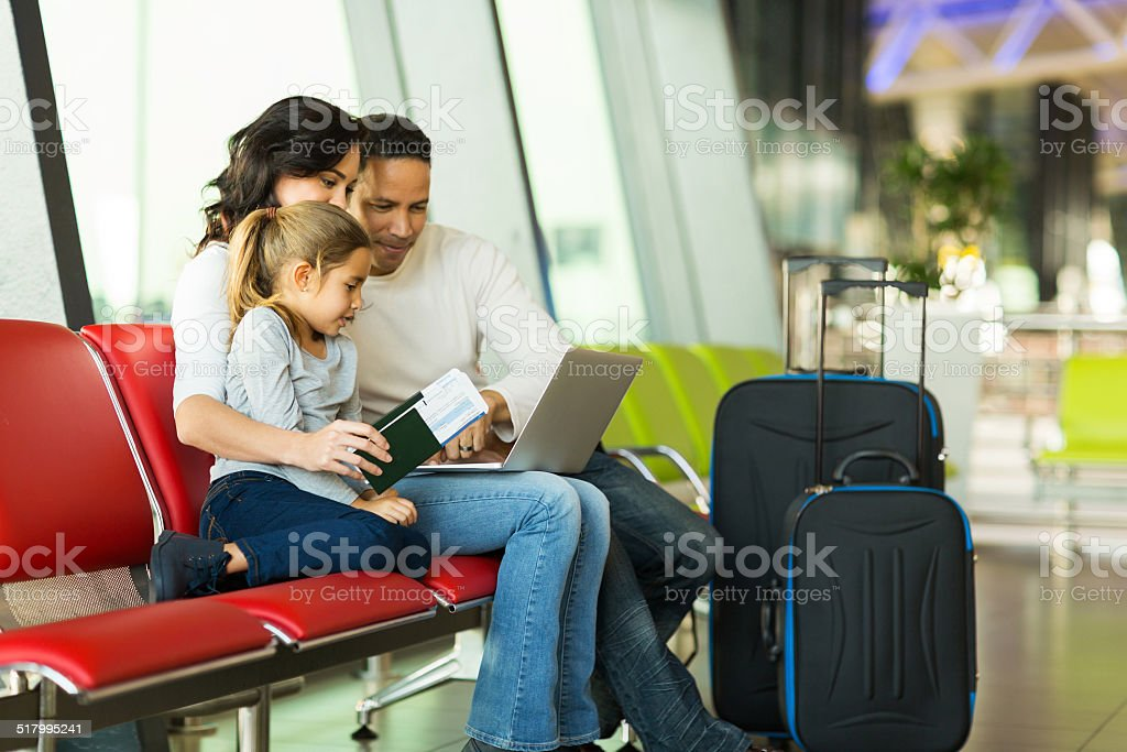 parents and daughter using laptop at airport stock photo