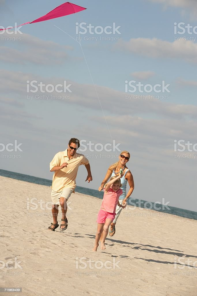 Parents and girl flying a kite royalty-free stock photo