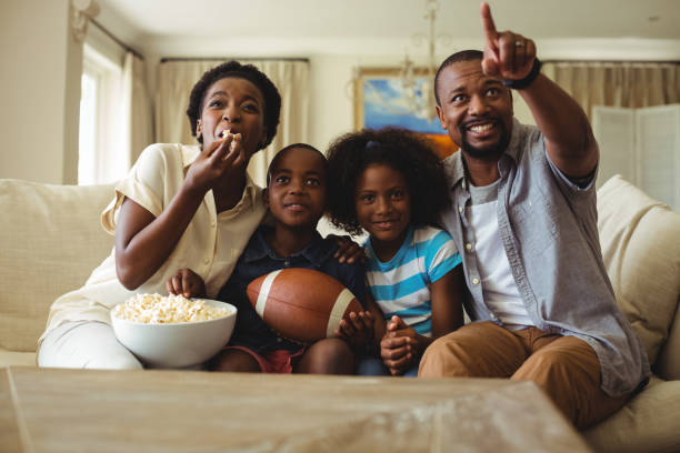 Parents and kids having fun while watching television in living room Parents and kids having fun while watching television in living room at home changing channels stock pictures, royalty-free photos & images