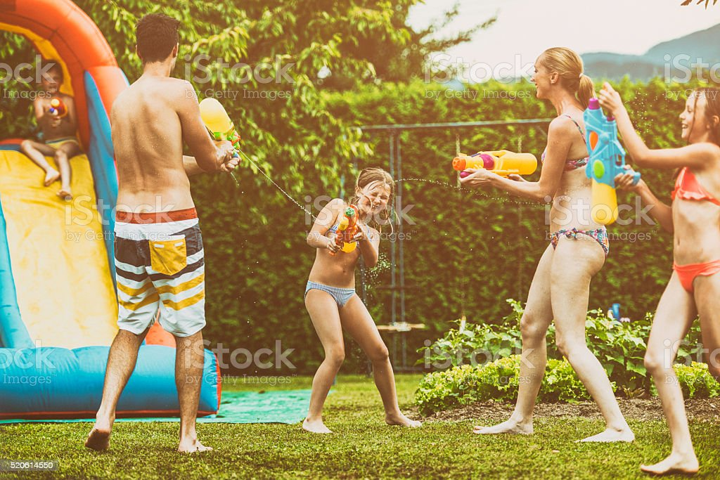 Parents and kids playing with squirt guns stock photo