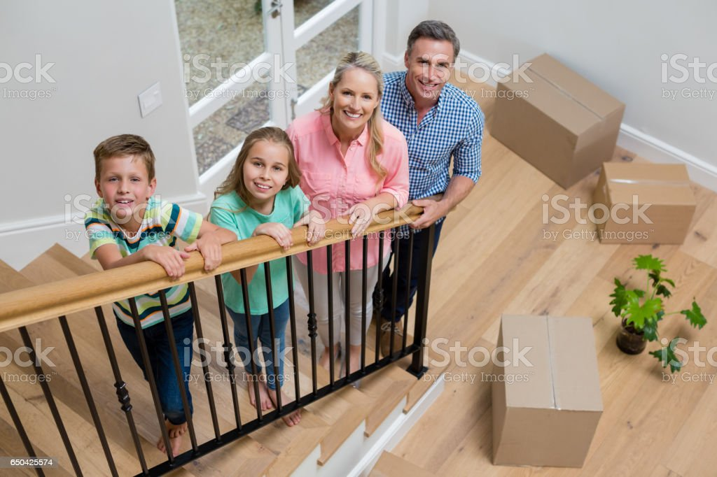 Parents and kids standing in staircase at home stock photo