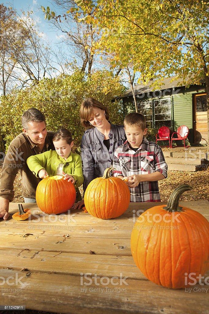 Parents and Playful Children with Halloween Pumpkin stock photo